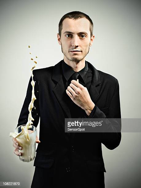 Young man in all black throwing glass of milk