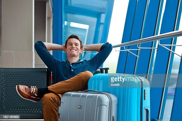 young man in an airport lounge - luggage stock pictures, royalty-free photos & images