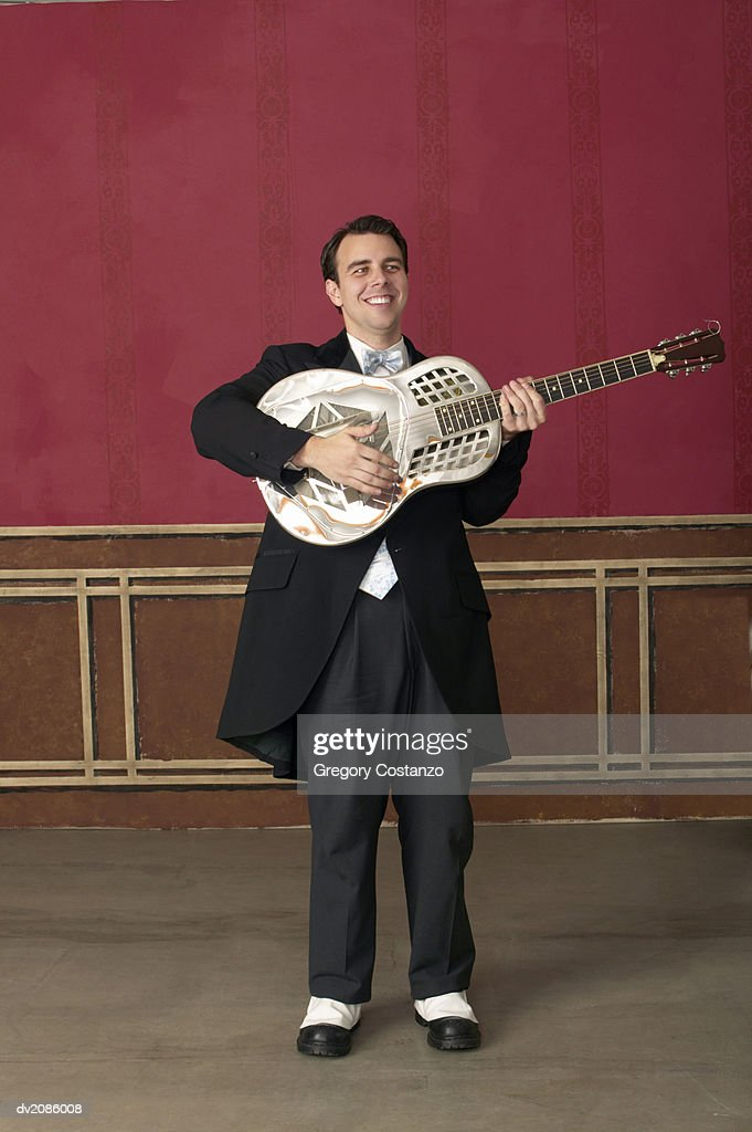 Young Man in an Old Fashioned Suit Stands on a Stage Playing a Guitar : Stock Photo