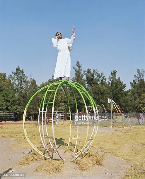 Young man in angel costume on playground sphere with mobile phone