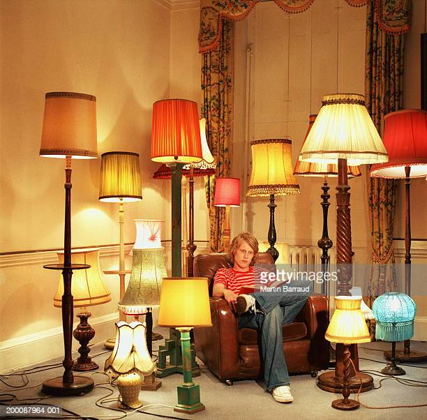 Young man in armchair reading book, surrounded by lamps