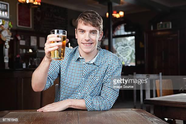 young man in bar - 手に持つ ストックフォトと画像