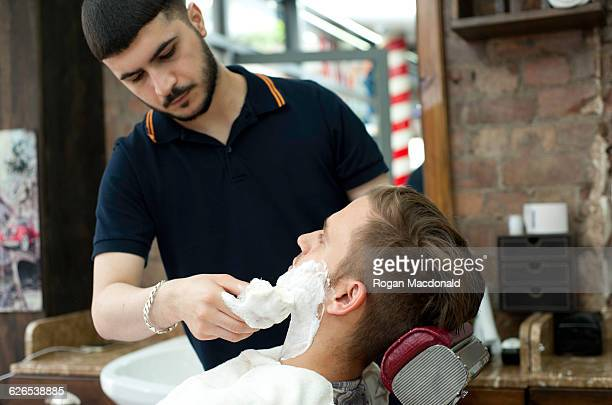 Young man in barbershop applying shaving cream to customers face