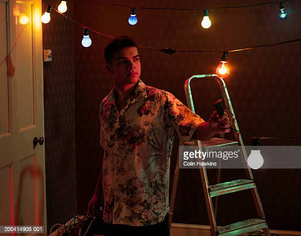 Young man in bare room holding cable attached to party lights