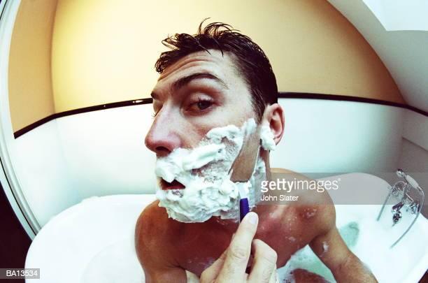 young man in bath wet shaving, wide angle view - weitwinkel stock-fotos und bilder