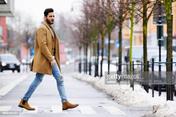 young man in beard crossing winter street - pedestrian crossing stock photos and pictures