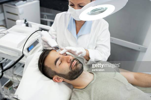 young man in beauty clinic receiving ultrasound facial cleaning procedure - beautician stock pictures, royalty-free photos & images