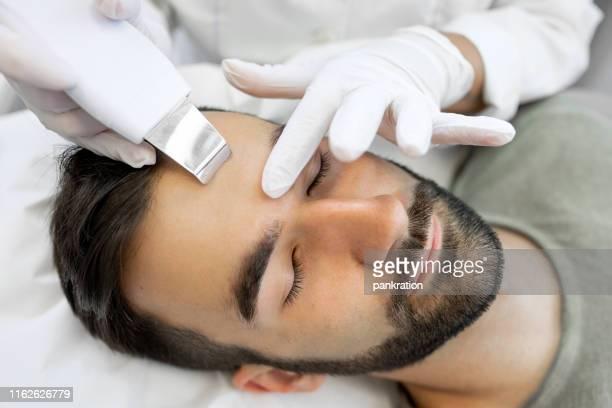 超音波顔のクリーニング手順を受け美容クリニックの若い男 - 美容整形手術 ストックフォトと画像