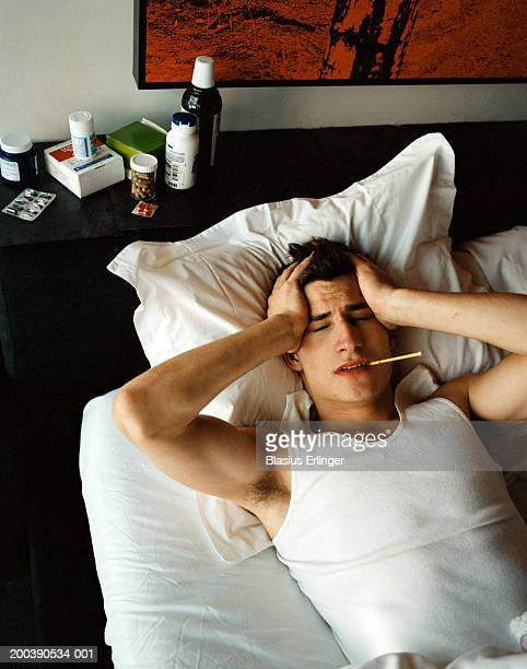 Young man in bed with thermometer in mouth holding head