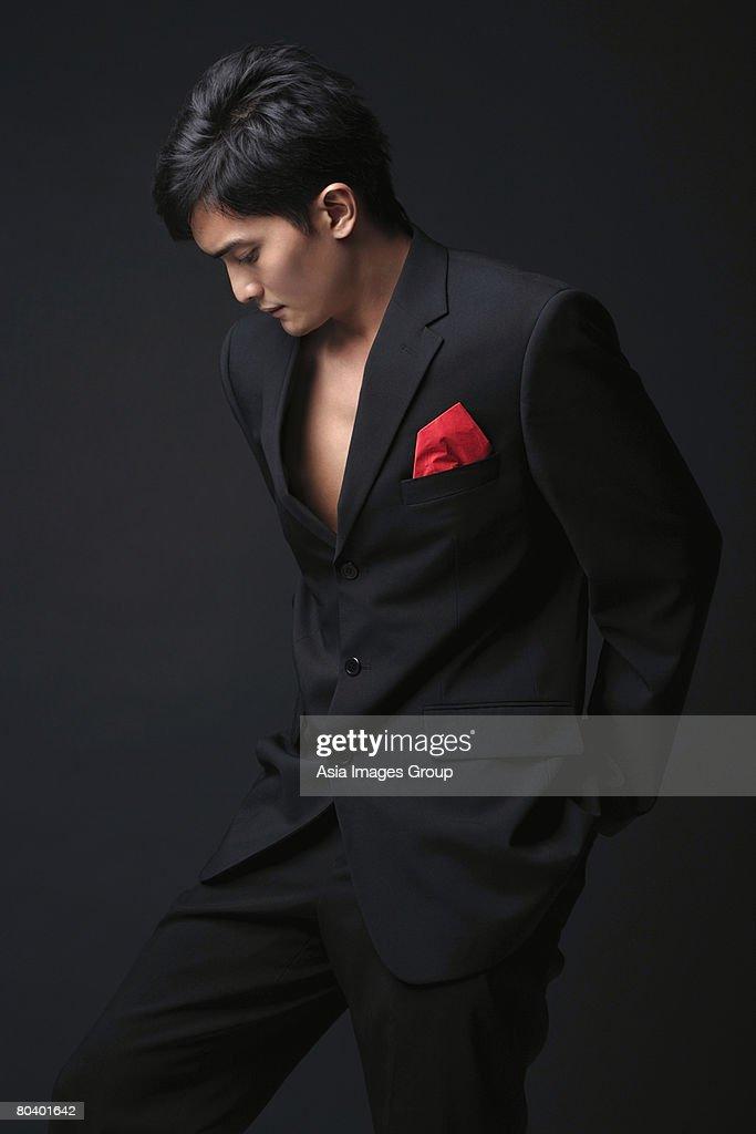 Young man in black suit looking down : Foto de stock
