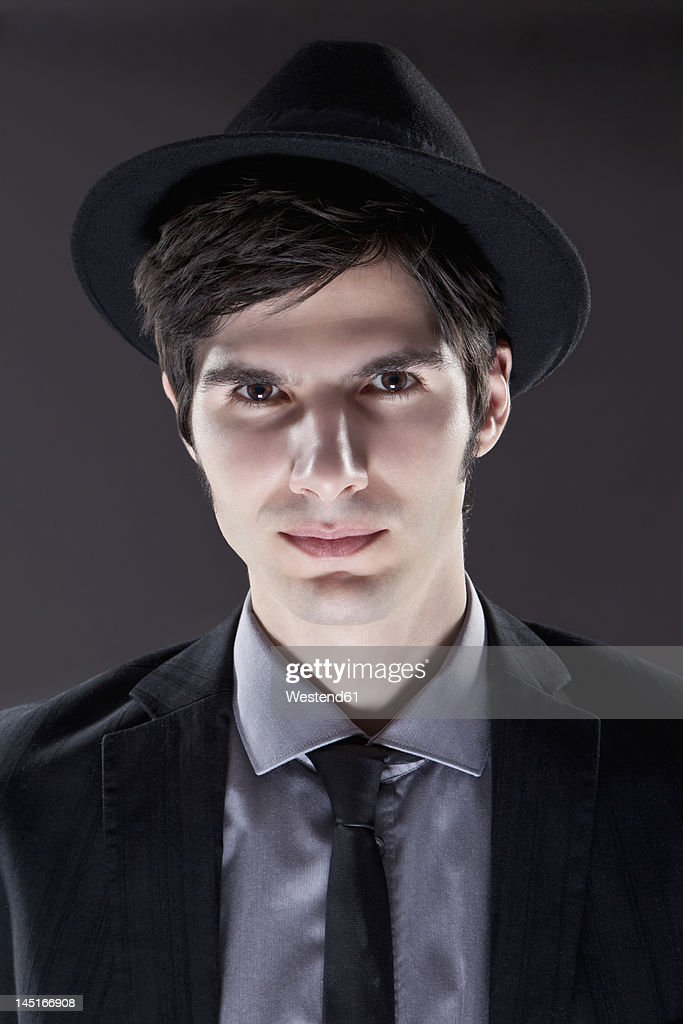 young man in black suit with hat portrait ストックフォト getty images