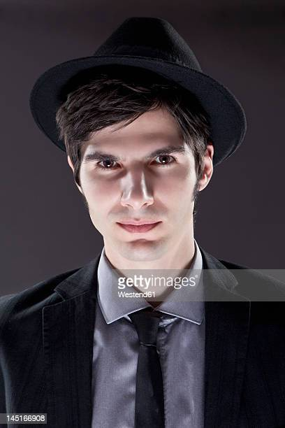 Young man in black suit with hat, portrait