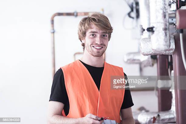 Young man in boiler room wearing high visibility vest looking at camera smiling