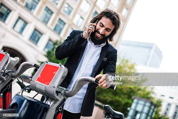 Young man in business taking city bike in London