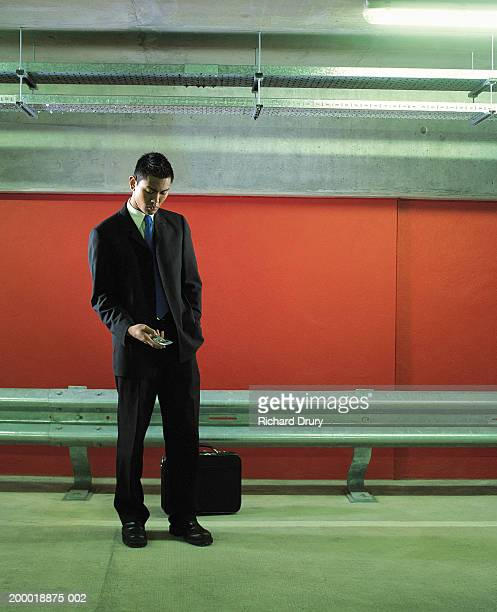 young man in car park keying on mobile phone - richard drury stock pictures, royalty-free photos & images