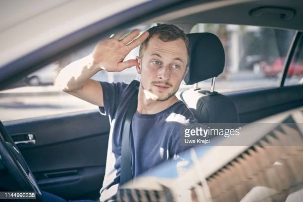 young man in car - waving stock pictures, royalty-free photos & images