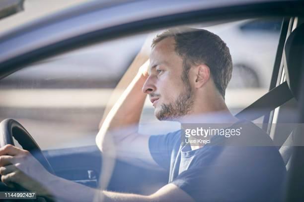 young man in car - noia foto e immagini stock