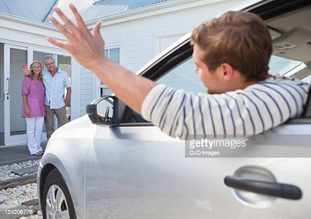 young man in car waving goodbye to parents - leaving stockfoto's en -beelden