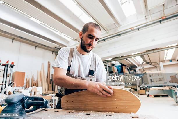 Young man in carpentry workshop looking down sanding skateboard