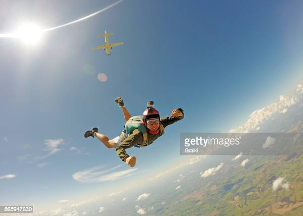 young man in casual clothes jumping from parachute. - スカイダイビング ストックフォトと画像