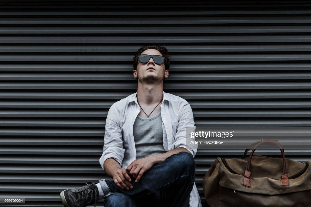 Young man in casual clothes resting.  Travel bag : Stock-Foto