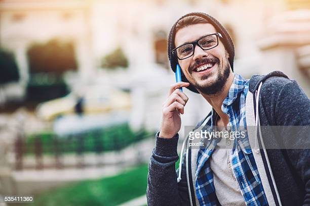 Young man in casual wear on the phone outdoors