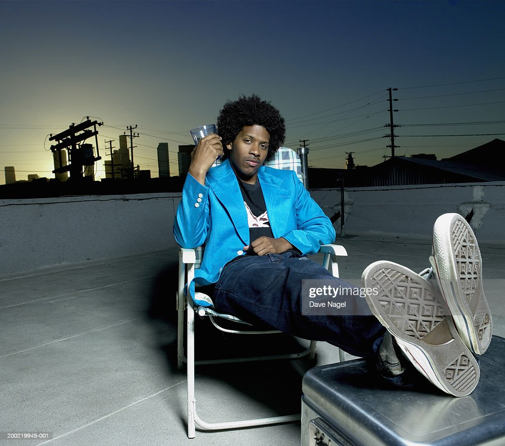 Young man in chair holding beverage on rooftop, portrait : Photo