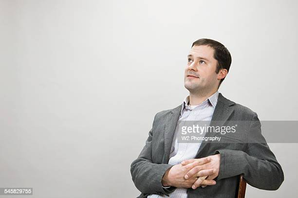young man in chair looking up - gray blazer stock pictures, royalty-free photos & images