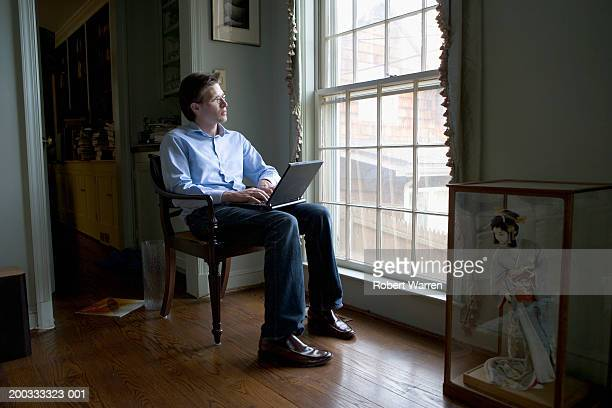 Young man in chair with laptop, looking out window
