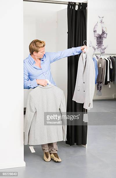 Young man in changing room, holding jackets