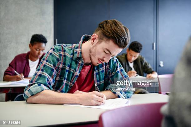 Young man in checked shirt doing college exam