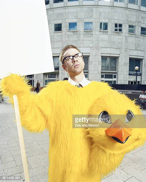 Young man in chicken suit, holding head under arm, placard in one hand