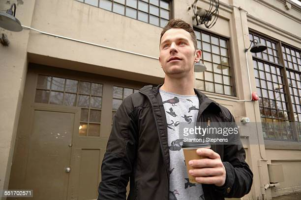 Young man in city drinking takeaway coffee