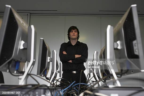 Young man in computer room, arms folded