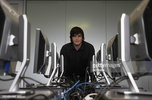 'Young man in computer room, portrait'
