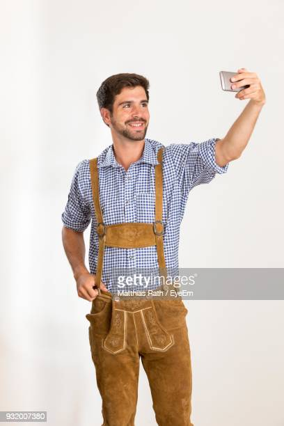 Young Man In Costume Taking Selfie Against White Background