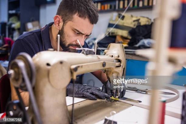young man in crafts repair shop focused on sewing using machine - serbia stock pictures, royalty-free photos & images