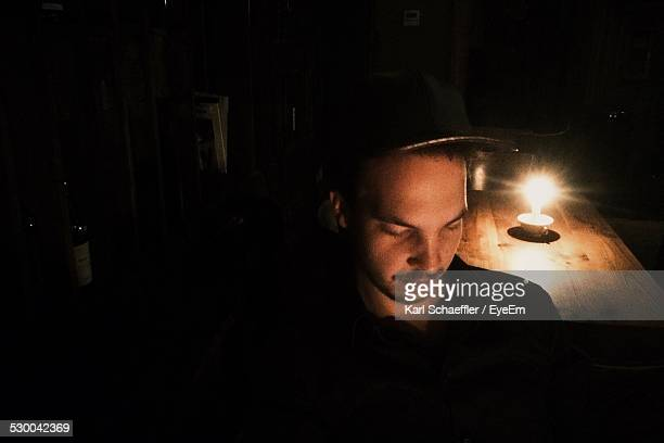 Young Man In Darkroom Against Lit Candle At Home