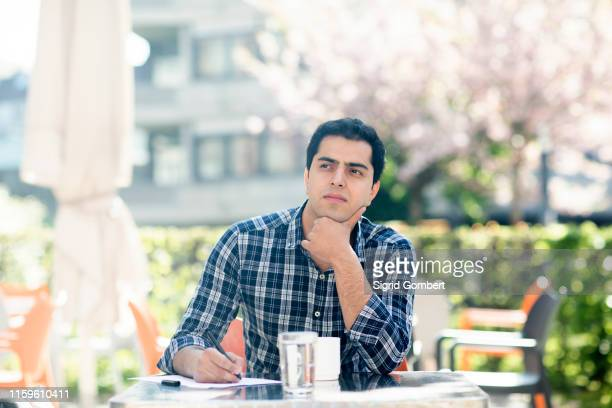 young man in deep thought at cafe - sigrid gombert stock-fotos und bilder