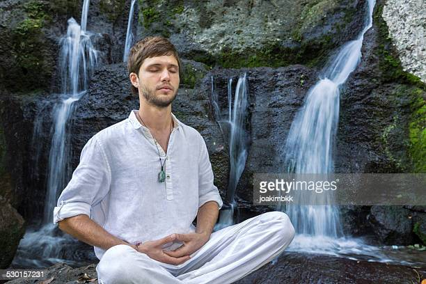 Young man in deep yoga meditation near waterfall