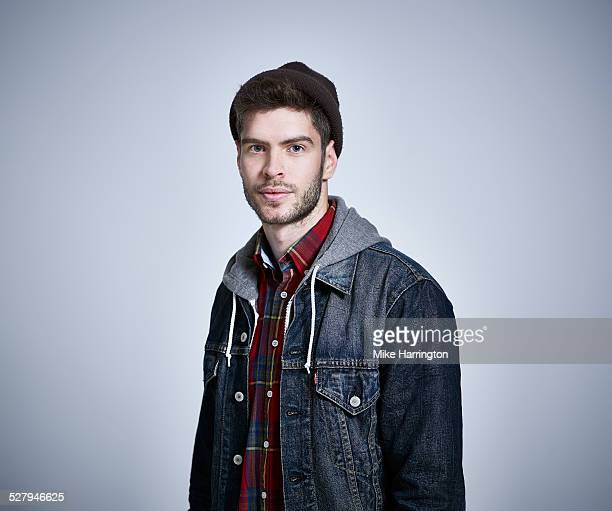 Young man in denim jacket looking to camera.