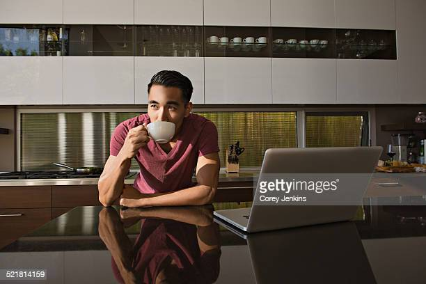 Young man in dining room drinking coffee