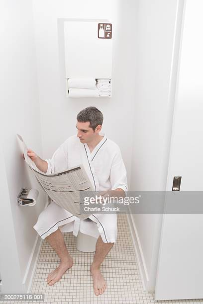 Young man in dressing gown reading newspaper on toilet in hotel bathroom