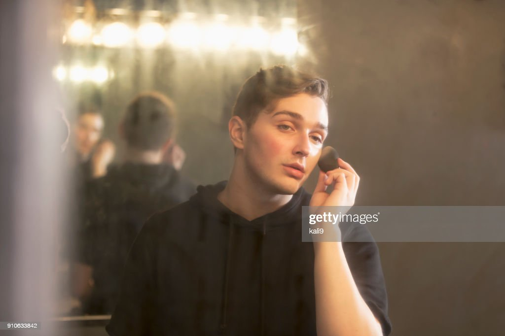 Young man in dressing room applying make-up : Stock Photo