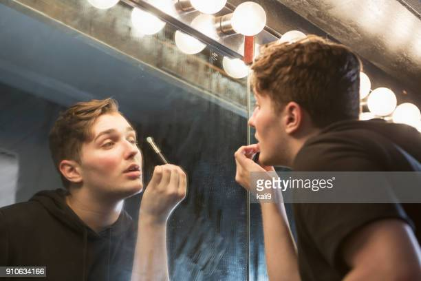 young man in dressing room applying make-up - stage make up stock photos and pictures