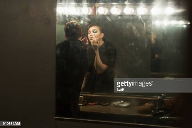 young man in dressing room applying make-up - young crossdressers stock photos and pictures