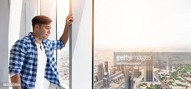 Young man in Dubai looking through a window