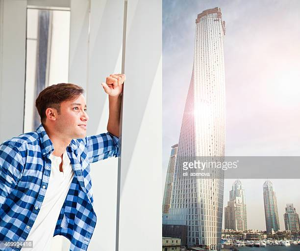Jeune homme à Dubaï de regarder par la fenêtre.