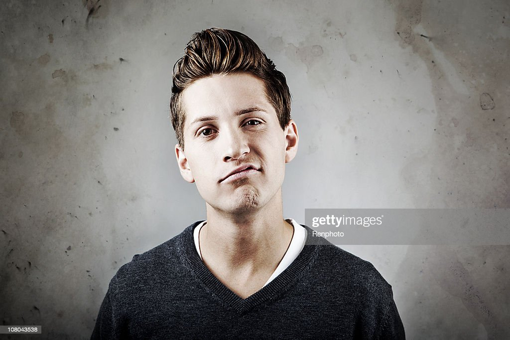 Young man in early 20s with smug expression : Stock Photo