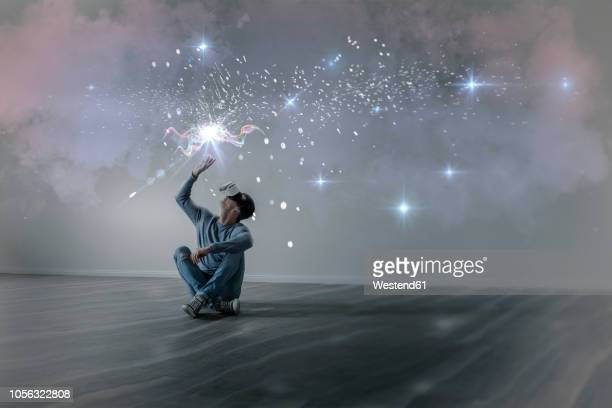 young man in empty apartment sitting on the floor using virtual reality glasses, composite - inspiratie stockfoto's en -beelden